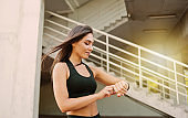 Attractive sport woman in sportswear use smart watch outdoors at urban environment