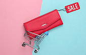 Shopping trolley and fashionable leather wallet with red sale tag on pink blue background. Top view. Discount. Minimalism