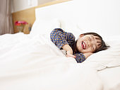 little asian girl laughing lying in bed