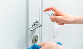 close up. neat man spraying antiseptic spray on the door handle