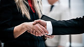 close up. businessman and businesswoman shaking hands with each other.