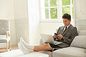 young asian businessman working at home using cellphone and laptop