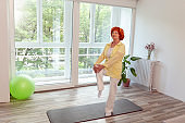 Elderly woman doing yoga session at home