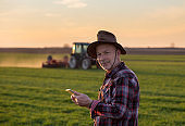 Farmer with tablet in field and tractor in background