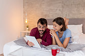 Couple drinking coffee and using tablet computer in bed
