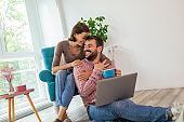 Couple cuddling and using laptop computer