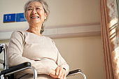 happy asian old woman sitting in wheel chair smiling