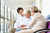 young asian doctor reviewing test result with senior couple patient