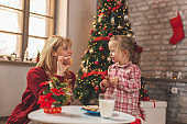 Mother and daughter drinking milk and eating gingerbread Christmas cookies