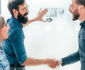 successful business partners shaking hands in the office
