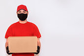 Delivery employee delivering cardboard box in medical gloves and mask.Сoncept of safety mail goods courier delivery in virus or coronavirus quarantine. Сopy space on white background