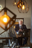 Senior businessman typing a text message