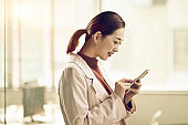 young asian business woman using mobile phone in office