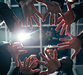 close up. group of young business people joining their palms in a circle