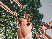 cheerful bride throws a wedding bouquet to her friends.