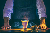 Bartender serving sparkling Baileys comet cocktail on fire