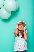 Little girl wearing headset listening to music