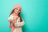 Little girl wearing knitted winter hat and scarf showing thumbs up