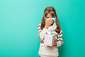 Child blowing nose into paper tissue while having flu