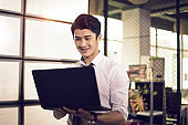 young asian business man looking at laptop smiling