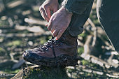 Hiker tying laces on boots