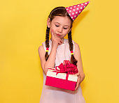 Thoughtful girl in dress looking at gift on hand and thinking about it isolated over yellow.Holiday concept.