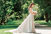 beautiful young woman in wedding dress standing in Park.