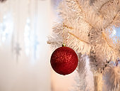 white Christmas tree with one red glass ball
