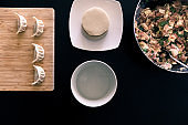 Filling, dough rounds, water and finished dumplings on cutting board