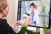 Video conferencing with doctor, woman compares medications