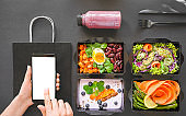 Female hand holding phone mock up white screen over vegan healthy food package vegetable delivery boxes black table background. Veggie diet nutrition menu order plan mobile app ad. Flat lay top view