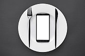 Smart phone mock up screen on white plate fork and knife black background table, food delivery app concept. Take away business restaurant meal online mobile application deliver order flat lay top view