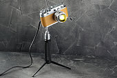 A vintage lamp made by me from an old film camera on a gray cement background.