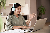 Happy indian teen girl student remote teacher tutor wear headphones video conference calling online, learning remote class webcam lesson looking at laptop virtual meeting working at home office.