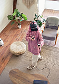 Hipster teen girl wear vr headset play virtual reality game, top vertical view.
