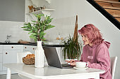 Happy teen girl pink hair using laptop sit at kitchen table having breakfast.