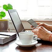Businessman, freelancer holding pen, using mobile smart phone, working on laptop computer at home