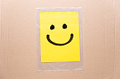 Drawing of a happy smiling emoticon on a yellow paper and transparent plastic bag with cardboard box background