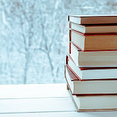 Old multi-colored books stand on a wooden shelf against the backdrop of the winter forest
