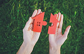 Red house with a shape of two parts of puzzle in human hands.