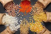 Different type of raw dry legumes composition. White beans, lentils, bulgur, chickpeas, kidney beans, corns, rice,  Mix organic legume concept