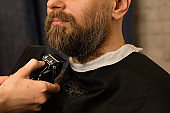 Barber trimming beard with electric razor