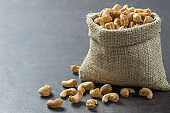 roasted salted raw cashew nuts in burlap sack on rustic table Healthy vegetarian snack, Anacardium occidentale