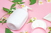 White plastic cosmetic container for moisturizing cream as a mock up with bright fresh jasmine flowers on light pink background. Body and skin care, health, wellness and beauty concept