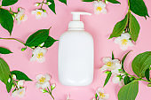 Top view of white plastic cosmetic container for moisturizing cream as a mock up with bright fresh jasmine flowers on pink background with copy space. Body and skin care and beauty concept