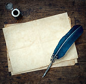 Old quill pen, and old paper blank sheet and vintage inkwell on wooden desk in the old office .