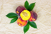 Top view of fresh juicy red, yellow and orange peaches with green leaves on light table background in summer season