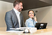 Two receptionists talking smiling at hotel front desk