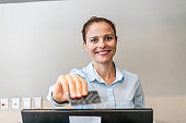 Portrait of a young female receptionist smiling at front desk of the hotel