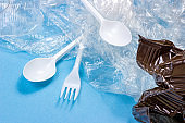 Crushed plastic spoons, forks, bottles and cups as a disposable waste on bright blue background. Environmental pollution and litter recycling concept